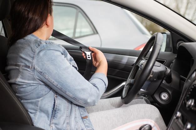 Autista donna cintura di sicurezza di fissaggio in macchina, contro l'incidente stradale, concetto di sicurezza, trasporto sicuro