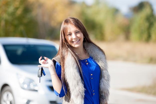 Driver donna sorridente mostrando nuove chiavi della macchina