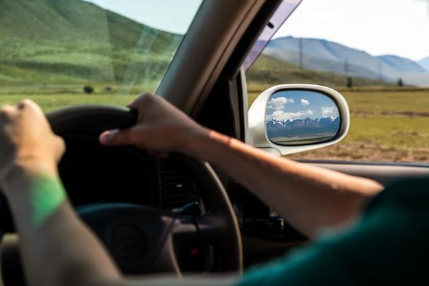 Guidare l'auto sulla strada di montagna. ragazzo all'interno dell'auto che guida sulla carreggiata di campagna tra campi con erba marrone e montagne innevate. il sole splende. spara da dietro.