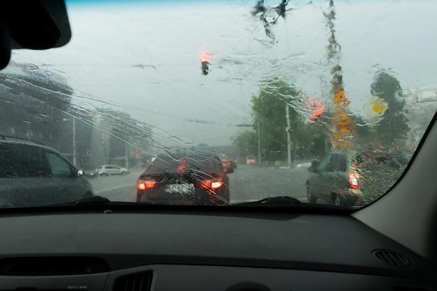 Guidare l'auto sotto la pioggia su strada bagnata. tempo piovoso attraverso il finestrino dell'auto. pioggia attraverso il parabrezza dell'auto in movimento. vista attraverso il finestrino dell'auto sotto la pioggia. tergicristalli dell'auto accesi sotto la pioggia.