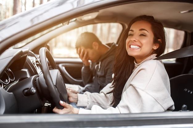 Istruzione di guida. una giovane donna impara a guidare una macchina. al suo istruttore o al suo ragazzo non piace il modo in cui guida un'auto. ma la ragazza è soddisfatta di se stessa e non ascolta il ragazzo.