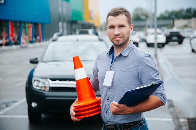 Istruttore di guida che raccoglie coni di plastica