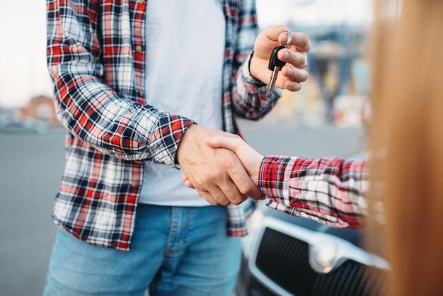 L'istruttore di guida dà la chiave dell'auto alla studentessa
