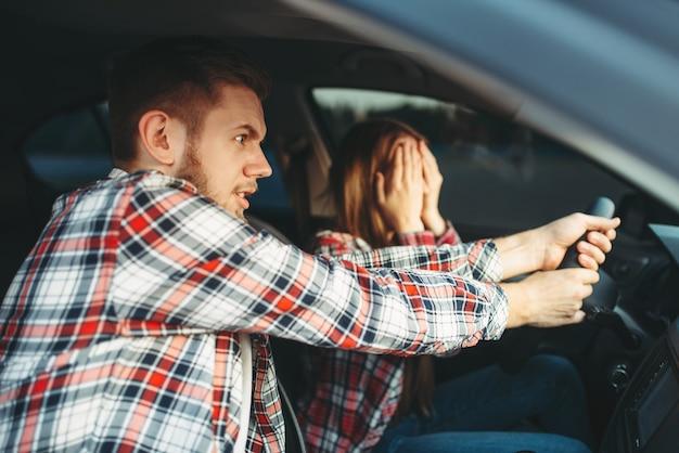 Istruttore di guida aiuta il conducente a evitare incidenti