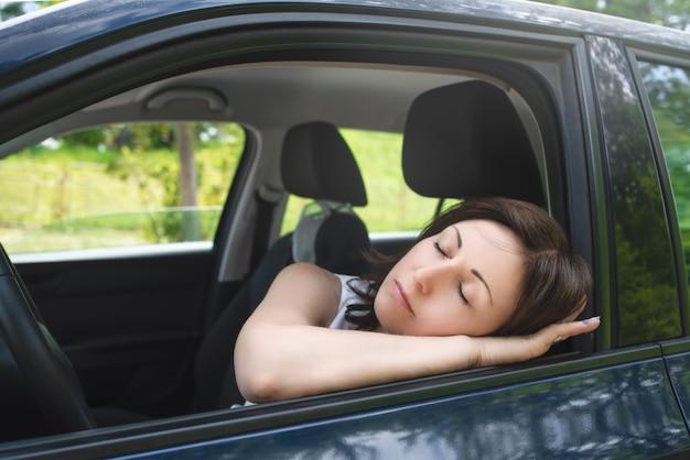Concetto di sicurezza di guida, donna molto stanca che dorme sul finestrino di una macchina e dorme al volante