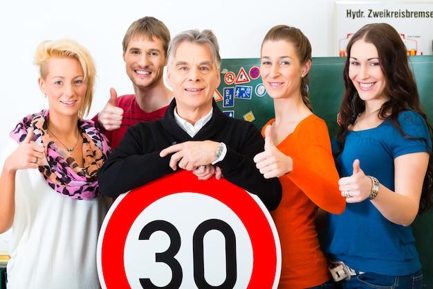 Scuola guida - istruttori di guida e studenti conducenti guardano un segnale stradale a tempo trenta
