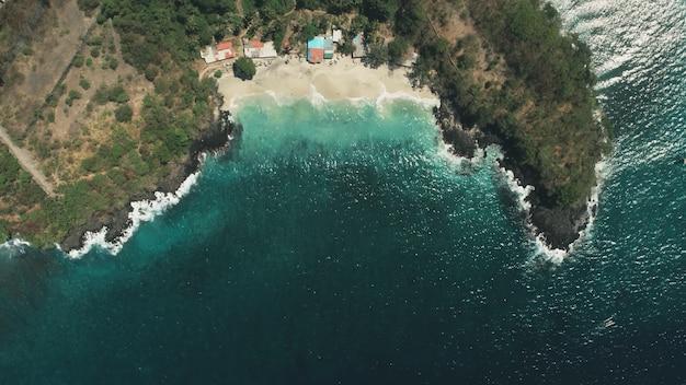 Onde della spiaggia dell'oceano di volo aereo del drone sul paesaggio di acqua cristallina di sabbia bianca nell'isola tropicale di bali