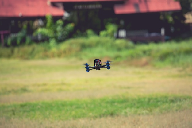 Drone elicottero che vola veloce con fotocamera digitale nel campo verde