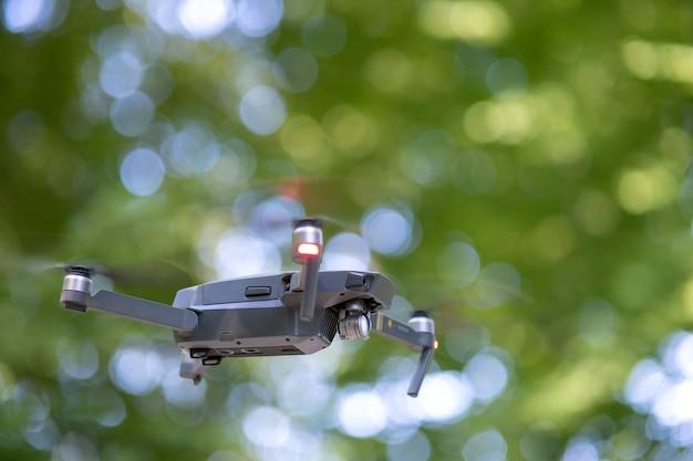 Drone elicottero con eliche sfocate e videocamera che volano in aria.