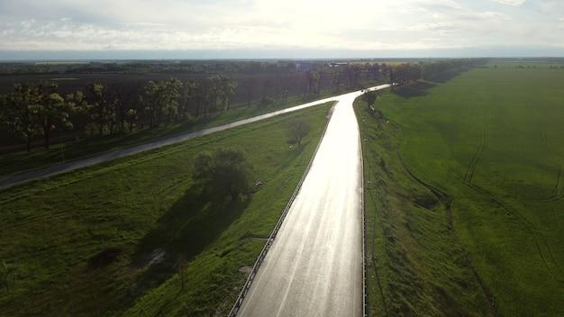 Il drone scende sopra la strada asfaltata bagnata per le auto tra i campi seminati