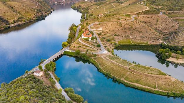 Drone occhio di rio circondato da montagne coltivate a vigneti con ponte e laghi