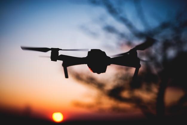 Drone che vola verso il tramonto. silhouette di drone contro il cielo colorato.