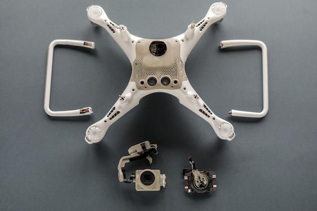 Drone su uno sfondo grigio con una fotocamera rotta. crash quadrocopter