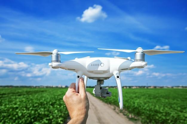 Drone in mano per un uomo su uno sfondo il campo verde