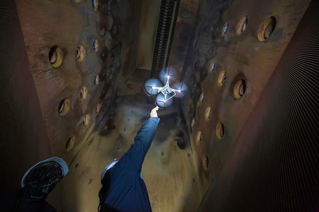 Ispezione di un drone maschile azionata da un operaio edile su una fornace in un sito confinato