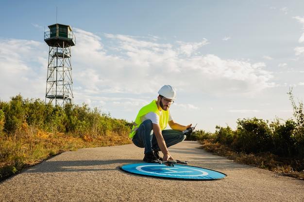 Uomo dell'operatore di droni lancio di un drone in un ambiente di campagna