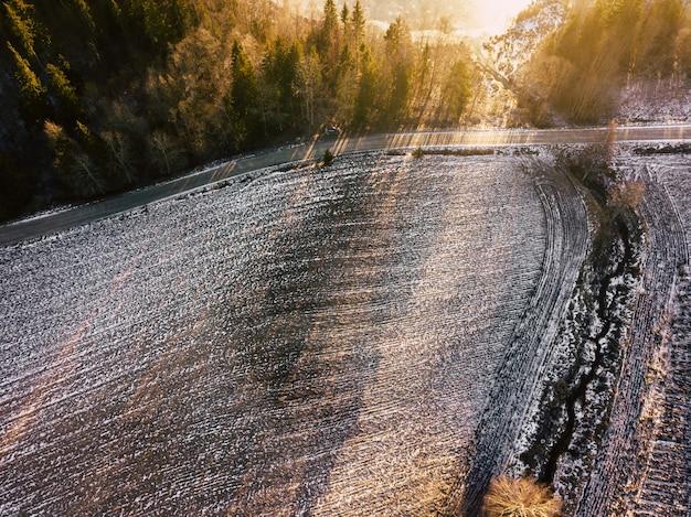 Foto con drone di campi e strade con la neve nell'ora d'oro