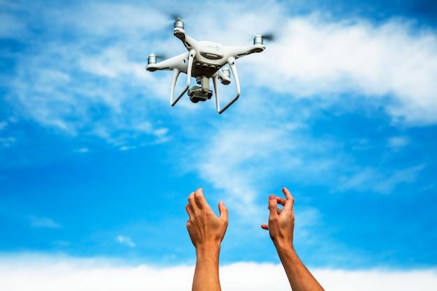 La donna del fotografo e del drone passa sul cielo blu
