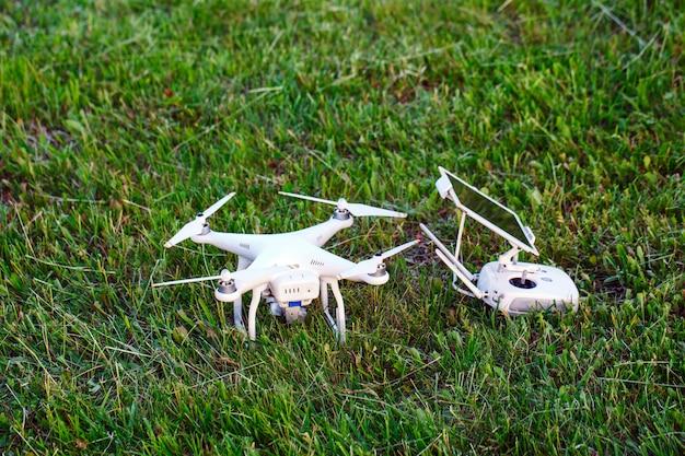 Elicottero quad drone con fotocamera digitale ad alta risoluzione e il suo pad telecomando con smartphone sull'erba