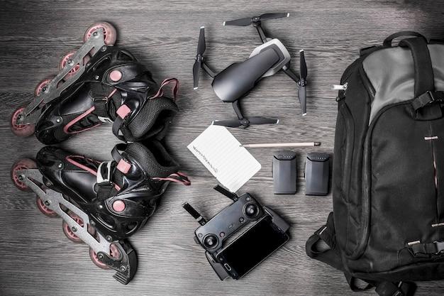 Drone e rulli, vicino a uno zaino e una batteria, con una foglia per la pianificazione, su uno sfondo legnoso, concetto di quadrocopter portatile