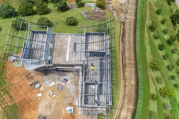 Vista del drone dall'alto in basso della costruzione del tetto in acciaio, operai edili al telaio metallico del tetto