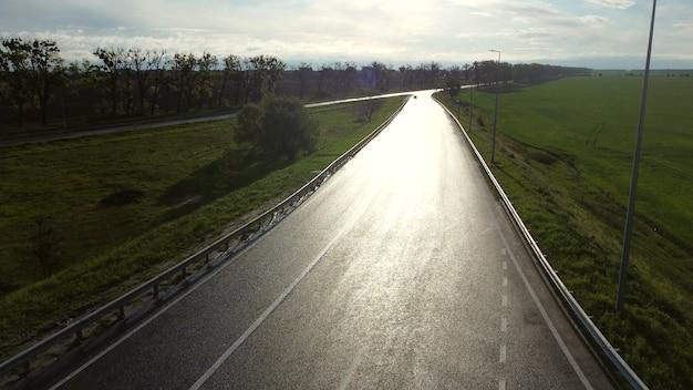 Drone sopra strada asfaltata bagnata per auto tra campi seminati in mattinata primaverile. strada asfaltata bagnata con sole riflettente, abbagliamento del sole. strada bagnata dopo la pioggia tra campi verdi. volo con vista aerea con drone