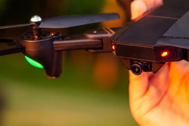 Primo piano della fotocamera dei droni su uno sfondo verde nella mano di un uomo