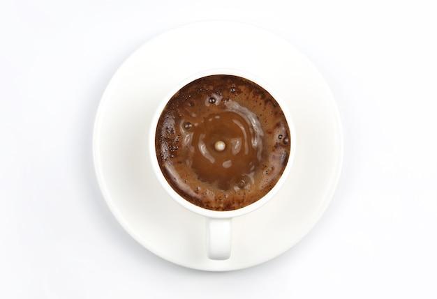 Goccia di latte che cade in una tazza bianca con caffè nero