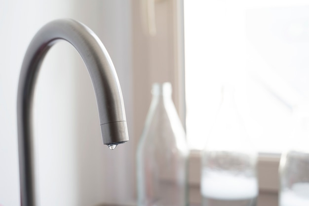 Goccia d'acqua appesa a un rubinetto in cucina a casa.