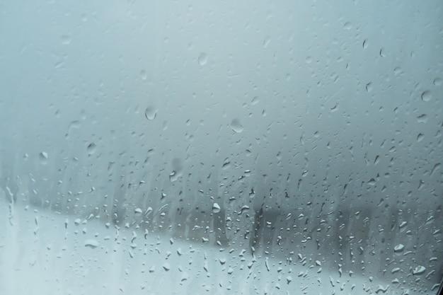 Gettare acqua sul vetro della finestra dalla condensa. goccia di pioggia sul fondo del vetro di finestra