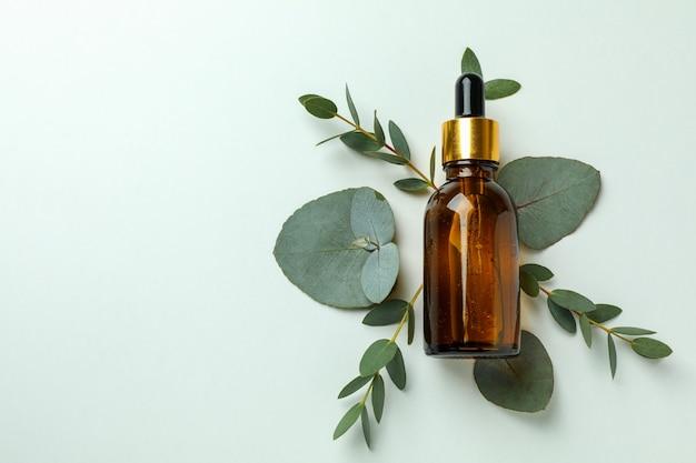 Flacone contagocce di olio di eucalipto e foglie su sfondo bianco