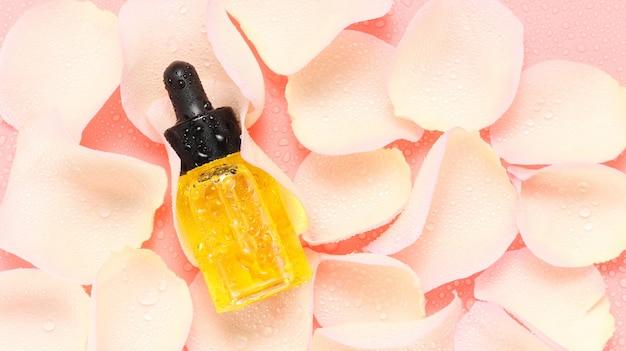Flacone contagocce di olio biologico per viso e corpo su petali di rosa bagnati con vista dall'alto su sfondo rosa
