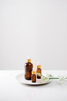 Flacone contagocce di olio puro di orchidea biologica su una superficie bianca con teste di orchidee sullo sfondo.