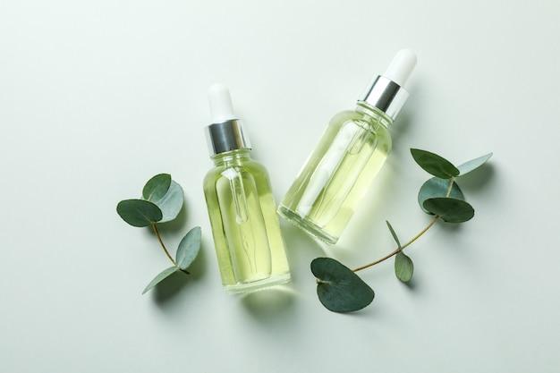 Bottiglie contagocce di olio di eucalipto e ramoscelli su sfondo bianco