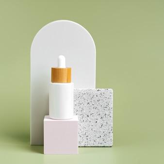 Bottiglie contagocce su sfondo quadrato color pastello a podio