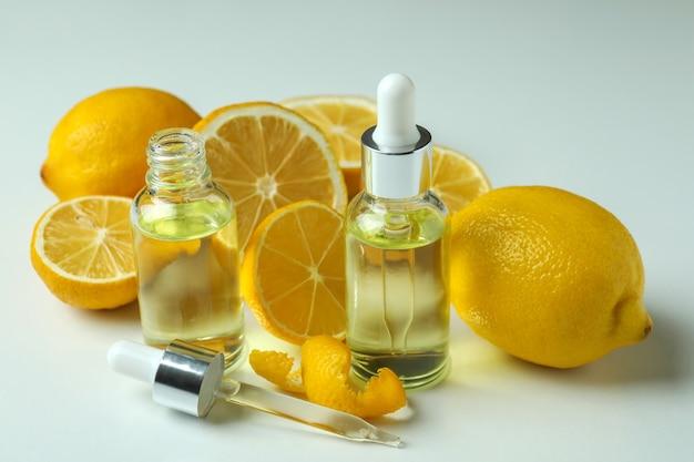 Bottiglie contagocce con olio e limoni su sfondo bianco isolato