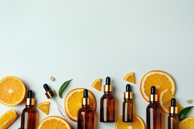 Bottiglie contagocce con olio e fette d'arancia su sfondo bianco