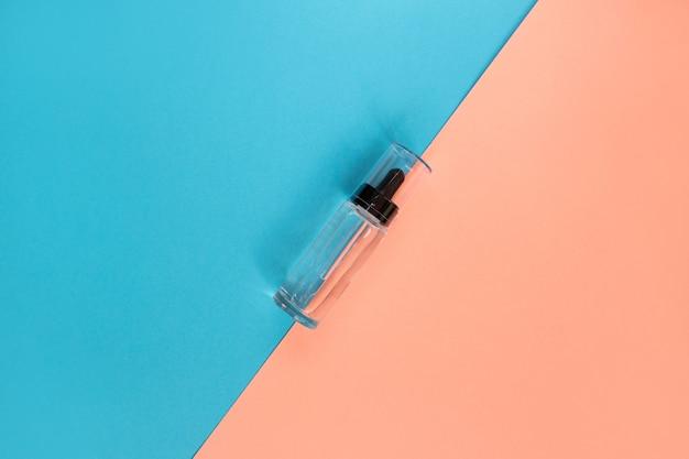 Bottiglia di vetro con contagocce. pipetta cosmetica su blu e rosa. lay piatto
