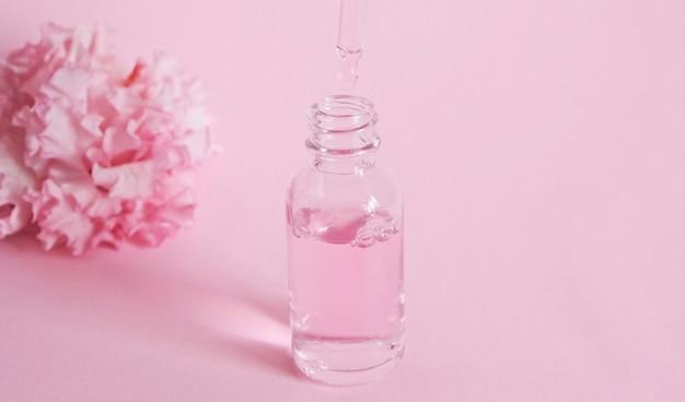 Flacone di vetro con contagocce con olio. bottiglia con una pipetta cosmetica. prodotto cosmetico idratante antietà. cura della pelle e del corpo. prodotto floreale all'essenza di olio rosa.