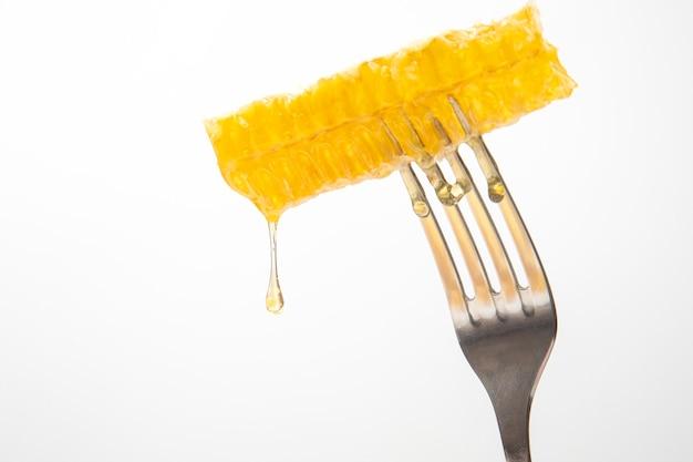 Gocce di miele fresco gocciolano dal miele di cera su una forchetta da tavola. nutrizione vitaminica e prodotto delle api