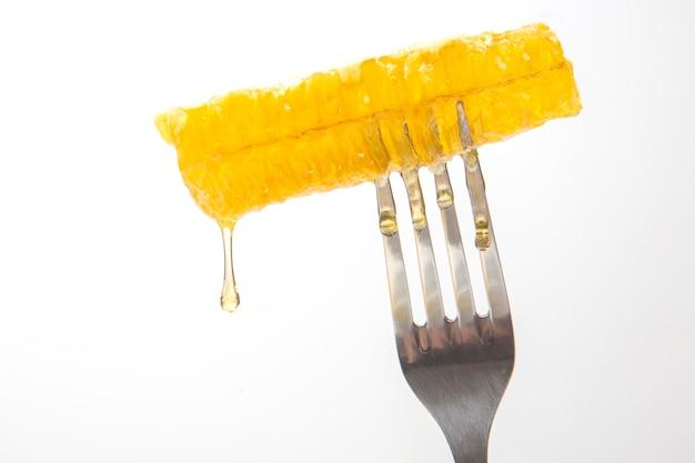 Gocce di miele fresco gocciolano dal miele di cera su una forchetta da tavola.