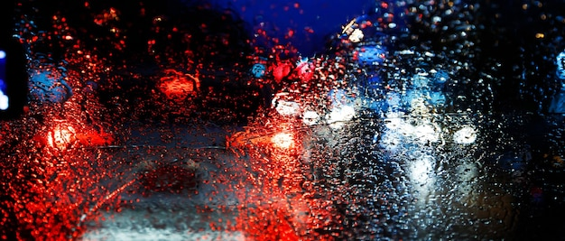 Gocce di pioggia pioggia sul parabrezza di vetro nella notte. strada sotto la pioggia battente. luce posteriore bokeh. focalizzazione morbida. si prega di guidare con prudenza, strada sdrucciolevole. focalizzazione morbida. auto ingorgo.