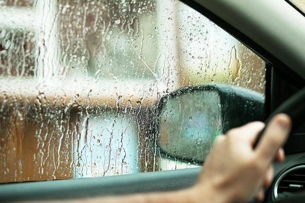 Gocce di pioggia sul finestrino dell'auto l'acqua cade dal finestrino del conducenteil concetto di maltempo