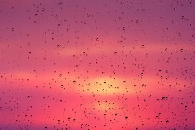 Gocce di pioggia su un vetro della finestra su uno sfondo di un pittoresco cielo al tramonto