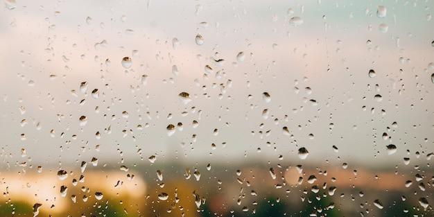 Gocce di pioggia sulla finestra. giorni di pioggia nel paesaggio della città. sfocato