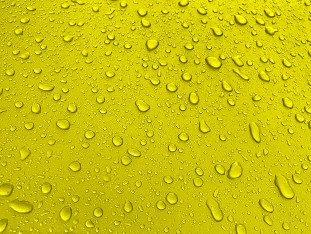 Gocce d'acqua su una superficie di metallo giallo, bellissimo sfondo dopo la pioggia