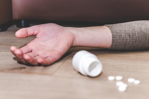 Abuso di droga o concetto di pillole di veleno. mano sul pavimento, pillole. suicidio per overdose di farmaci e tossicodipendenti.