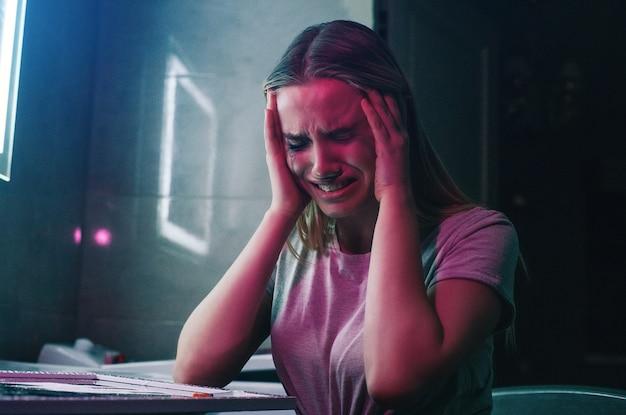 Ossessione e dolore da droga. il tossicodipendente tiene le mani sulla sua mano e sta impazzendo vicino alle droghe. solo una donna tossicodipendente con il trucco imbrattato piange nella toilette del night club.