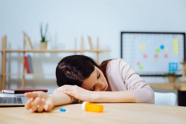 Effetto collaterale del farmaco. ragazza stanca che mette la testa sul braccio destro e tiene gli occhi chiusi mentre è seduto sul posto di lavoro