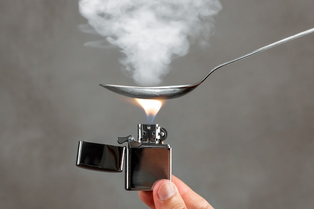 I farmaci vengono preparati in un cucchiaio con un accendino sotto di esso